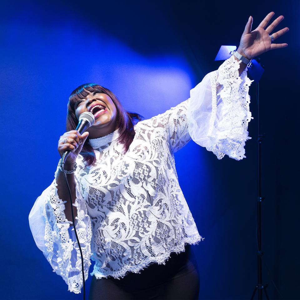 Shemekia Copeland on stage in a white lace blouse